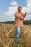 Modern farmer with scythe. At ripe wheat field Stock Photo