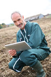 Modern farmer using tablet in middle of field Royalty Free Stock Photo