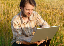 Modern farmer on wheat field with laptop. Happy smiling modern forty years old farmer checking his wheat field and working on laptop computer Royalty Free Stock Photography
