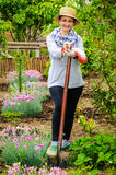 Modern farmer woman spade working backyard garden cellphone Royalty Free Stock Photo