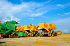 Modern farming equipment. Modern harvester combine and trucks during harvest time at Paddy field near Sekinchang Malaysia Royalty Free Stock Photography