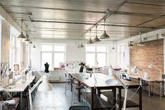 Modern Fashion  Atelier Interior. Wide angle shot of modern atelier interior with wooden workstation in foreground and sewing dummies, no people, copy space Royalty Free Stock Image