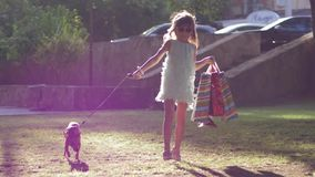 Modern fashion girl walking with dog on leash after shopping with packages in hand outdoors in sunrays. Modern fashion girl walking with dog on leash after stock footage