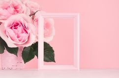 Modern fashion Valentine days background - blank frame for advertising and rich pink roses on white wood board, copy space. stock photo
