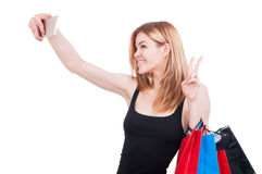 Modern fashionable lady taking self portrait. With her cell phone while she`s on shopping isolated on white Stock Images