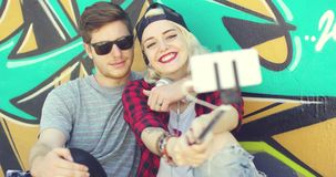 Modern fashionable young couple taking a selfie. As they pose sitting together in front of a colorful graffiti covered wall stock footage