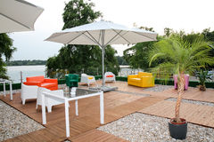 Modern fashioned patio cafe lounge. With umbrella and comfortable chairs royalty free stock photos