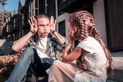 Modern father making funny faces while entertaining his little daughter stock image