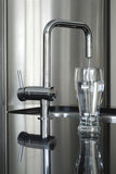 Modern faucet and glass of water Stock Image