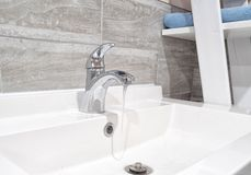 Modern faucet with running water royalty free stock images