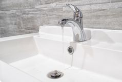 Modern faucet with running water stock images