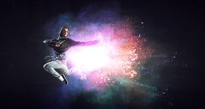 Modern female dancer jumping in hoodie with colourful splashes background. Mixed media. Modern female dancer in hoodie in action with colourful splashes stock photography
