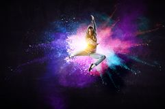 Modern female dancer jumping in hoodie with colourful splashes background. Mixed media. Modern female dancer in hoodie in action with colourful splashes stock image