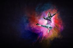 Modern female dancer jumping in hoodie with colourful splashes background. Mixed media. Modern female dancer in hoodie in action with colourful splashes royalty free stock photos