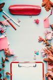 Modern female home office desktop in pink red color with flowers and accessories on blue background,top view, frame. Flat lay Stock Photos