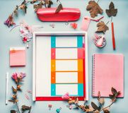 Modern female home office desktop in pink red color with flowers , accessories and planner wallet on blue background,top view. Fla. T lay, mock up Royalty Free Stock Photo
