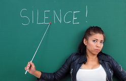 Modern female teacher asks for silence stock photography