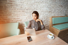 Modern female watching fashion news on touch pad while waiting order in cafe. Young beautiful woman reading electronic book via internet on digital tablet while Stock Photography