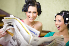 Modern feminist movement. Two young housewifes reading newspaper and looking for some cheap things Stock Photography
