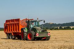 Modern Fendt tractor pulling orange trailer Royalty Free Stock Image