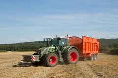 Modern Fendt tractor pulling orange trailer Royalty Free Stock Photo