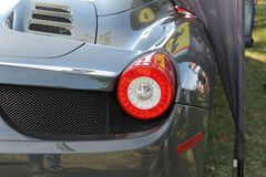 Modern Ferrari rear end closeup detail. Rear view. mid-engined Ferrari 458 Spider luxury sportscar rear view parked on lawn on a sunny day in Boca Raton, south stock photos