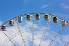 Modern Ferris wheel against a blue sky with clouds stock image