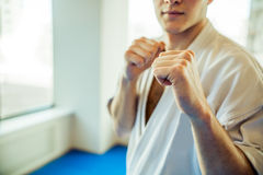 Modern fight club. Karate fighter in judogi standing in a fight club, ready to fight, close-up Royalty Free Stock Photos
