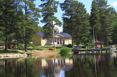 Finland, Savonia/Kuopio: Modern Finnish Home. A modern Finnish house (built in 2010) at a lake in Savonia, surrounded by pines, with dock, boat, flagpole, and Stock Photos