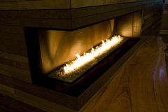 Modern fireplace home hotel. A modern big fireplace with a long bench Royalty Free Stock Images