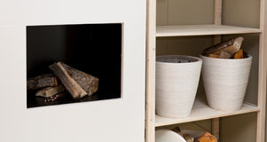 Modern fireplace. Modern interior detail - fireplace and shelves for keeping firewood Stock Photos