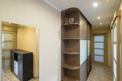 Interior of the flat. Warm tones, wooden floor. Built-in wardrobe. Modern flat interior with laminate and warm tones. Built-in wardrobe Royalty Free Stock Images