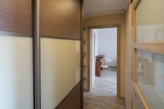 Interior of the flat. Warm tones, wooden floor. Built-in wardrobe. Modern flat interior with laminate and warm tones. Built-in wardrobe Stock Photos