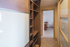 Interior of the flat. Warm tones, wooden floor. Built-in wardrobe. Modern flat interior with laminate and warm tones. Built-in wardrobe Royalty Free Stock Photo