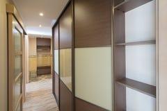 Interior of the flat. Warm tones, wooden floor. Built-in wardrobe. Modern flat interior with laminate and warm tones. Built-in wardrobe Stock Images