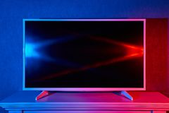 A flat TV lit with red and blue colors. A modern flat LED TV on a stand is lit in red and blue colors Royalty Free Stock Photography