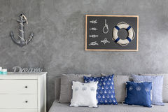 Modern flat with nautical decorations. Sofa with pattern pillows and white commode stock images