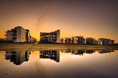 Modern flats. Modern seaside flats in a design district under night sky with reflections on water Royalty Free Stock Photo