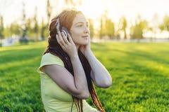 Modern flicka med dreadlocks som lyssnar till musik med hennes hörlurar i hösten Sunny Park Favorit- musik, lycklig tid arkivbild