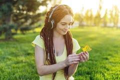 Modern flicka med dreadlocks som lyssnar till musik med hennes hörlurar i hösten Sunny Park Favorit- musik, lycklig tid royaltyfri bild