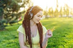 Modern flicka med dreadlocks som lyssnar till musik med hennes hörlurar i hösten Sunny Park Favorit- musik, lycklig tid royaltyfri fotografi