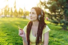 Modern flicka med dreadlocks som lyssnar till musik med hennes hörlurar i hösten Sunny Park Favorit- musik, lycklig tid fotografering för bildbyråer