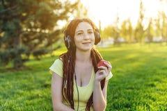 Modern flicka med dreadlocks som lyssnar till musik med hennes hörlurar i hösten Sunny Park Favorit- musik, lycklig tid arkivfoton
