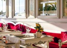 Modern flott italiensk restaurangmatsal med vita tabeller och röda sammetkuddar royaltyfri foto
