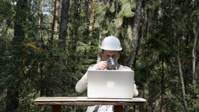 Modern forester works in the woods on a laptop