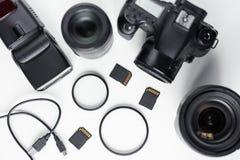 Modern fotokamera, linser och utrustning över den vita tabellen arkivbilder