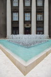 Modern fountain. Fountain in front of a dark building with four ionic volutes,  Zagreb, Croatia. Built in 1927, by the prominent Croatian architect Viktor Stock Photos