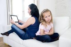 Modern för knarkaren för internetnätverket som använder det digitala minnestavlablocket som ignorerar den lilla ledsna dottern, l Royaltyfri Bild