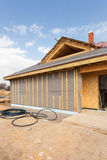 Modern frame energy efficient house under construction with membrane coverings, roof shingles and insulation materials. Modern frame energy efficient house Royalty Free Stock Photography