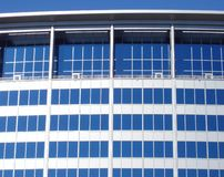 Modern framework. Detail of glass windows on a modern commercial building in downtown Baltimore, Maryland, reflecting a blue summer sky Stock Images